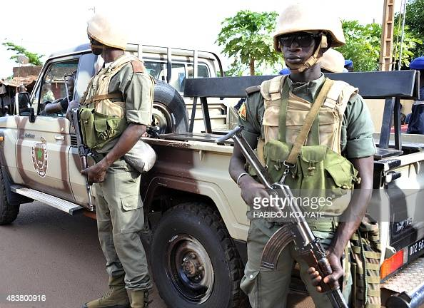 Armed soldiers stand next to a pickup truck on August 13 2015 near the site in Mali's capital Bamako where a policeman and a civilian were wounded on...