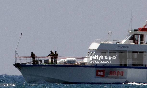 Armed soldiers stand on the bow of a boat as it enters the northern entrance of the port of Ashdod on May 31 following the storming by Israeli navy...