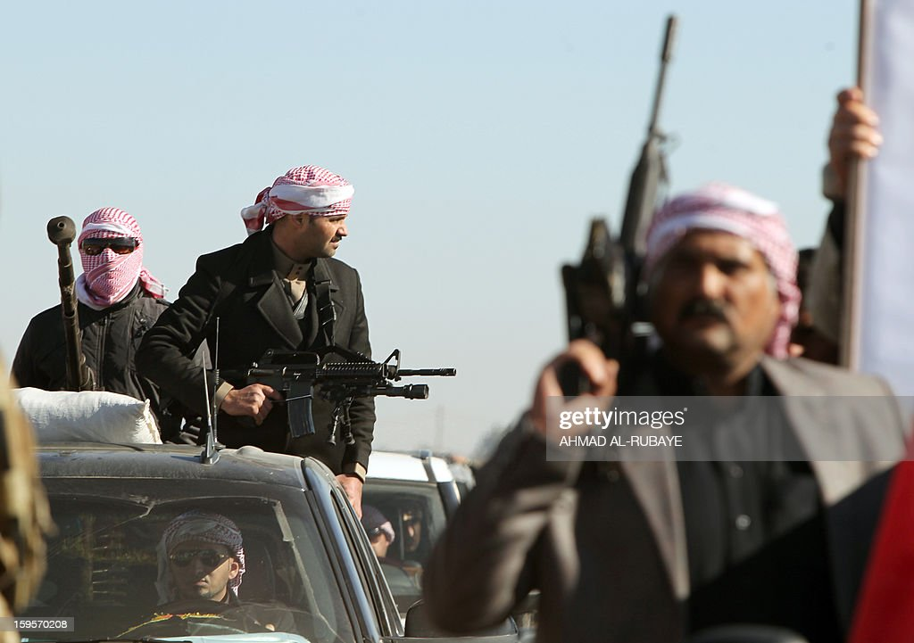 Armed supporters take part in the funeral procession of MP Ayfan Saadun al-Essawi, of the secular Sunni-backed Iraqiya bloc, in the western town of Fallujah, 50 kilometers from Baghdad, on January 16, 2013, in Anbar province. Essawi, 37-years-old, was killed by a suicide bomber who wrapped his arms around the lawmaker before blowing himself up, as a political crisis engulfed Iraq. AFP PHOTO/AHMAD AL-RUBAYE