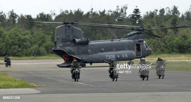 Armed Taiwanese soldiers ride on motorcycles next to a USmade CH47 helicopter during the 'Han Kuang' lifefire drill some 7 kms from the city of...