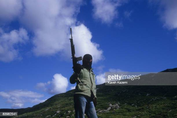 Armed with with an M16 automatic assault rifle a trainee member of the Provisional Irish Republican Army stands guard on a hilltop while his comrades...