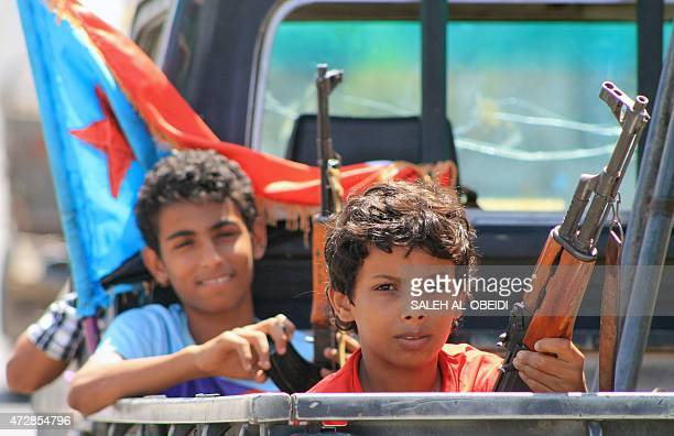 Armed Yemeni children sit in the back of a pick up truck with fighters loyal to Yemen's Saudibacked President Abedrabbo Mansour Hadi in the Dar saad...