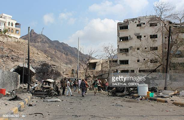 Armed Yemeni men look at the wreckage of a vehicle on January 18 in the aftermath of a suicide car bombing on the residence of Aden's police chief...