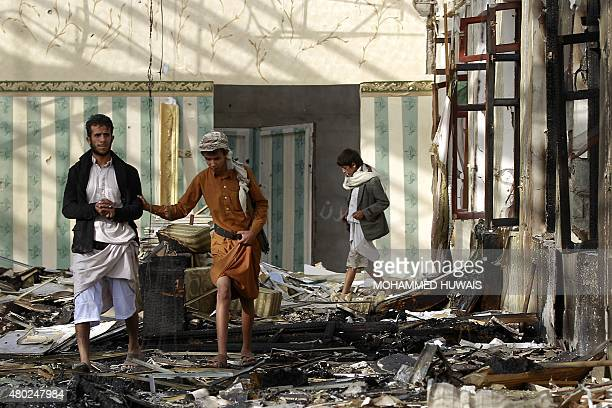 Armed Yemenis walk on the rubble of a wedding hall which was reportedly hit by a Saudiled coalition air strike in the capital Sanaa on July 10 a few...
