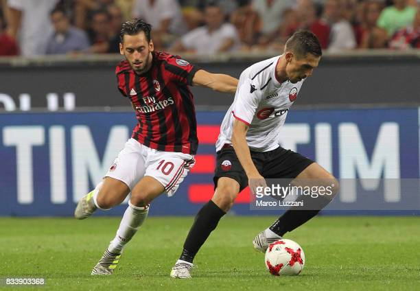 Armend Alimi of KF Shkendija 79 is challenged by Hakan Calhanoglu of AC Milan during the UEFA Europa League Qualifying PlayOffs round first leg match...