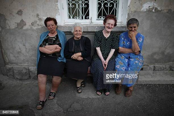 Armenia woman are sitting on a bench in front of an apartment house