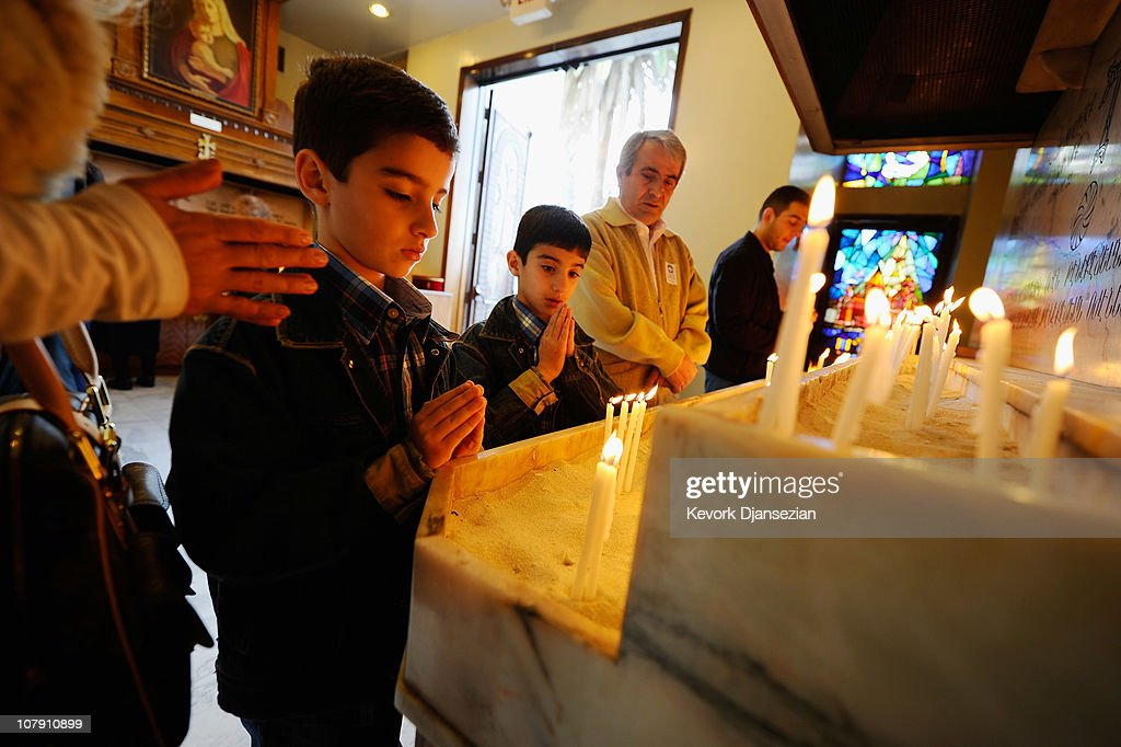 Armenian children pray after lighting candles at St Garabed Armenian Apostolic Church during Christmas mass on January 6 2011 in Los Angeles...