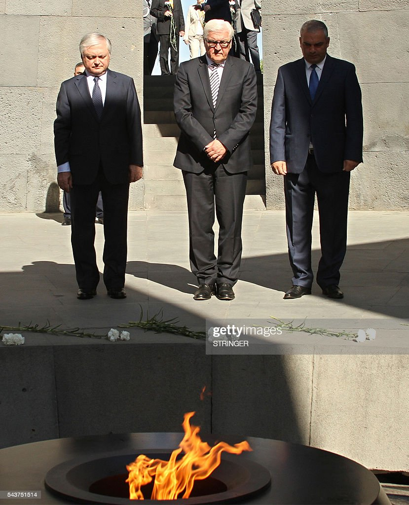 Armenian Foreign Minister Edward Nalbandian (L) and his German counterpart Frank-Walter Steinmeier (C), who currently chairs the Organisation for Security and Cooperation in Europe (OSCE) monitoring body attend a ceremony in commemoration of Armenians killed by Ottoman forces during World War I at the Tsitsernakaberd Genocide Memorial in Yerevan on June 30, 2016. / AFP / stringer