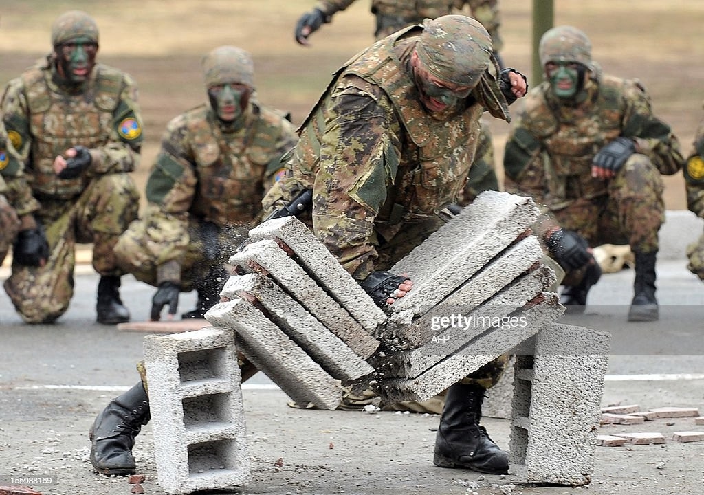 Armenian military scouts watch a soldier break cement blocks during celebrations of the 20th anniversary of formation of the reconnaissance troops of the Armed Forces at Qanaqer military unit in Yerevan on November 10, 2012.
