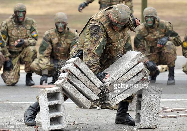 Armenian military scouts watch a soldier break cement blocks during celebrations of the 20th anniversary of formation of the reconnaissance troops of...