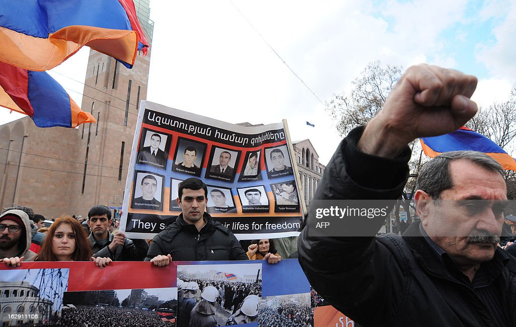 Armenian opposition supporters carry flags and posters during a rally devoted to the memory of killed fellow fighters in Yerevan on March 1, 2013. The rally takes place at Freedom Square - the scene of mass protests in 2008 which ended in violence and left 10 people dead.