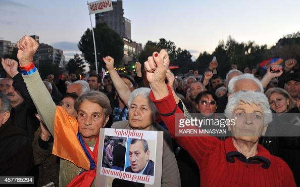 Armenian opposition supporters raise their fists during a rally in Yerevan on October 24 2014 AFP PHOTO / KAREN MINASYAN
