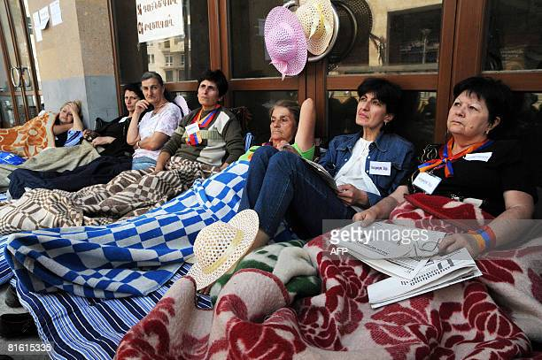 Armenian opposition supporters sit on a sidewalk in the center of Yerevan during a women's hunger strike on June 18 2008 Women are demanding that the...