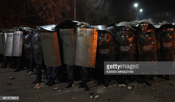 Armenian police officers hold up their shields as they stand guard during clashes with protesters at a demonstration near the Russian Consulate...