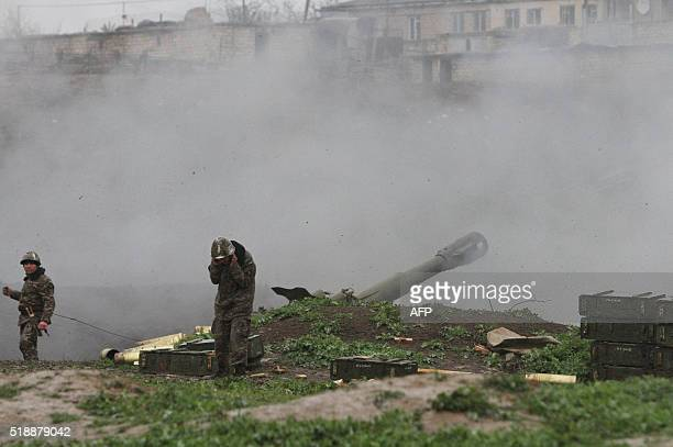 Armenian servicemen of the selfdefense army of NagornoKarabakh fire an artillery shell towards Azeri forces from their positions in the town of...