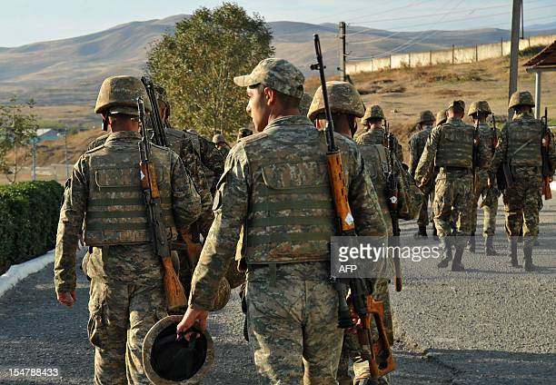 Armenian soldiers of the selfproclaimed republic of NagornoKarabagh walk near the frontline on the border with Azerbaijan on October 25 2012...