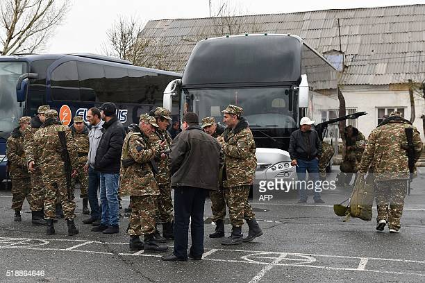 Armenian volunteers wearing military fatigues and holding their weapons wait next to buses in Yerevan on April 3 2016 before heading to the Karabakh...