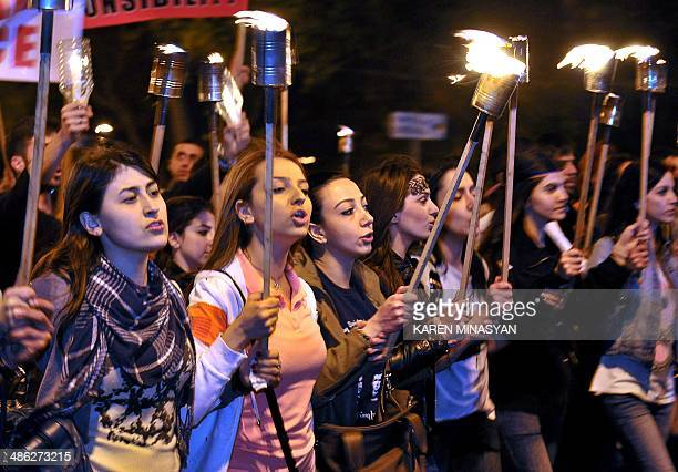 Armenian women carry torches to commemorate the 99th anniversary of the Ottoman Turkish massacre of Armenians in Yerevan on April 23 2014 Turkish...