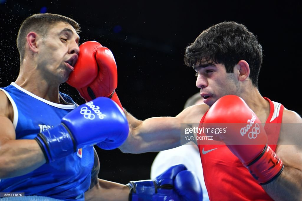 TOPSHOT Armenia's Artur Hovhannisyan lands a punch on Spain's Samuel Carmona Heredia during the Men's Light Fly match at the Rio 2016 Olympic Games...