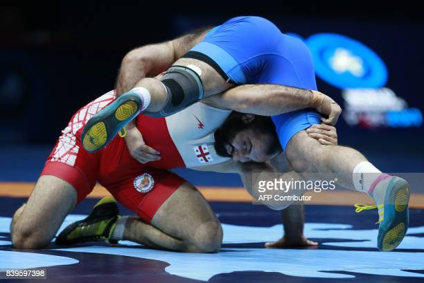 Armenia's Georgi Ketoev challenges Georgia's Elizbar Odikadze during the men's freestyle wrestling 97kg category bronze medal playoffs at the FILA...