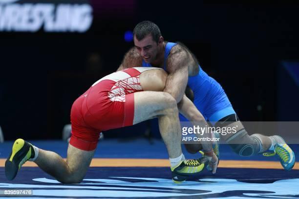 Armenia's Georgi Ketoev challenges Georgia's Elizbar Odikadze during the men's freestyle wrestling 97kg category bronze medal playoffs at the FILA...