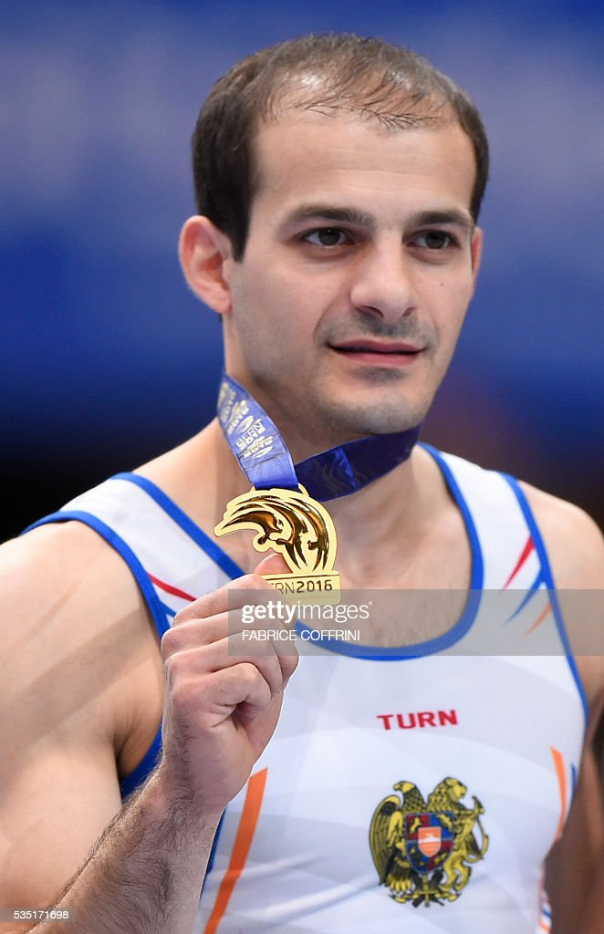 Armenias Harutyun Merdinyan (1st) celebrates on the podium after the Mens Pommel Horse competition of the European Artistic Gymnastics Championships 2016 in Bern, Switzerland on May 29, 2016. / AFP / FABRICE