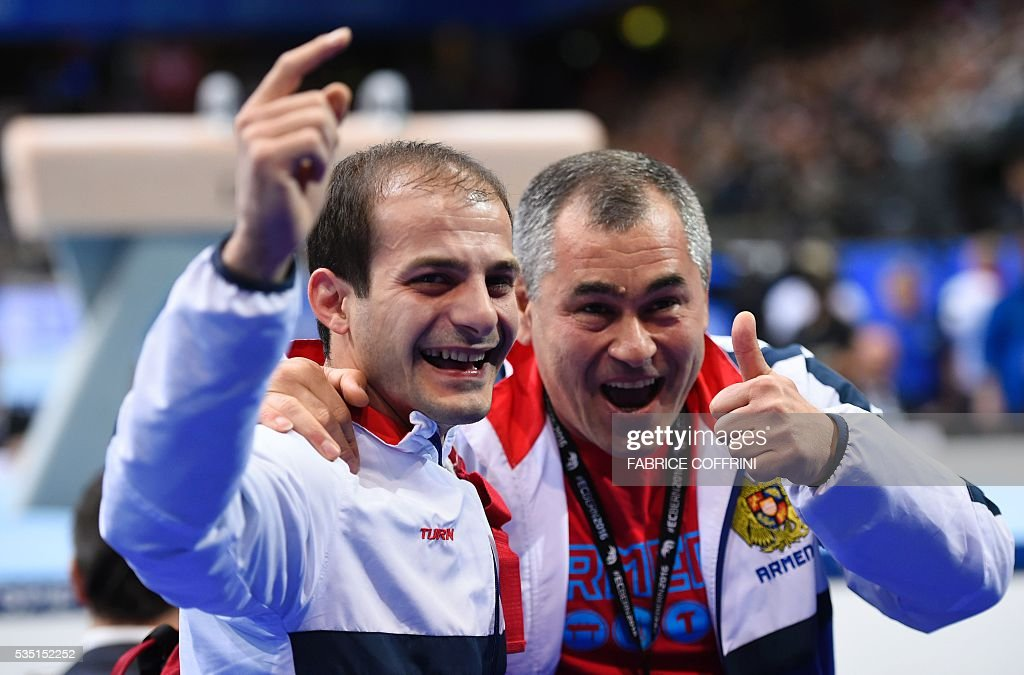 Armenias Harutyun Merdinyan celebrates winning with his caoch Hakob Serobyan (R) after the Mens Pommel Horse competition of the European Artistic Gymnastics Championships 2016 in Bern, Switzerland on May 29, 2016. / AFP / FABRICE