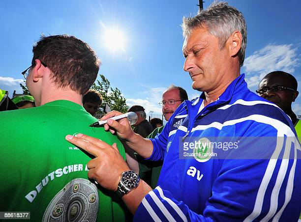 Armin Veh Head Coach of VfL Wolfsburg signs autographs for fans after the first training session of the new season at the Volkswagen Arena on June 22...