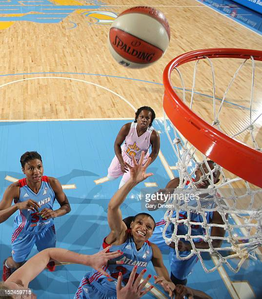 Arminte Price of the Atlanta Dream goes to the basket past teammate Angel McCoughtry and Carolyn Swords and Epiphanny Prince of the Chicago Sky on...