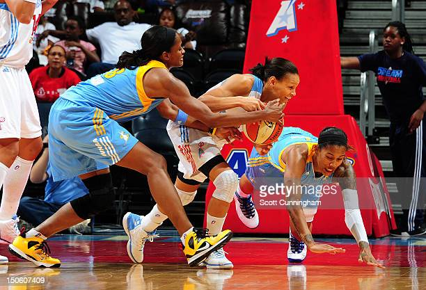 Armintie Price of the Atlanta Dream battles for a loose ball against Swin Cash and Tamera Young of the Chicago Sky at Philips Arena on August 22 2012...
