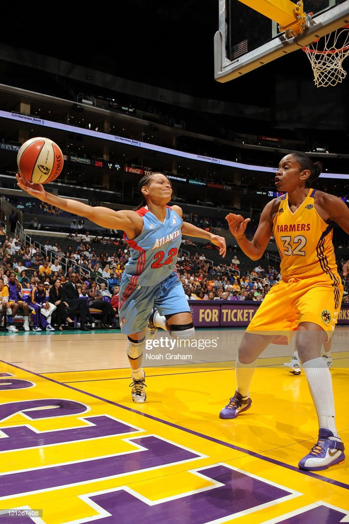 Armintie Price #22 of the Atlanta Dream passes around Tina Thompson #32 of the Los Angeles Sparks during a game at Staples Center on August 16, 2011 in Los Angeles, California.