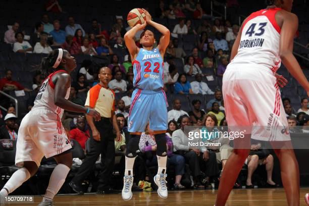 Armintie Price of the Atlanta Dream shoots against Ashley Robinson of the Washington Mystics at the Verizon Center on August 24 2012 in Washington DC...