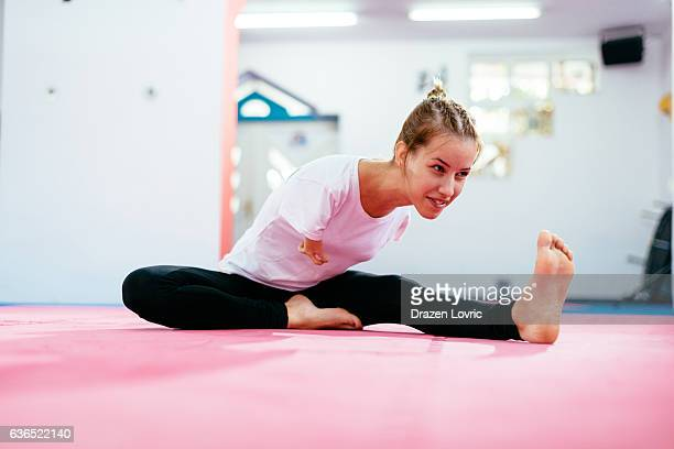 Armless sportswoman warming up for martial arts training
