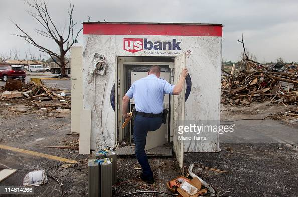 Armored car courier Josh Beck works on salvaging cash from an ATM which was damaged and tossed approximately 20 feet when a massive tornado passed...