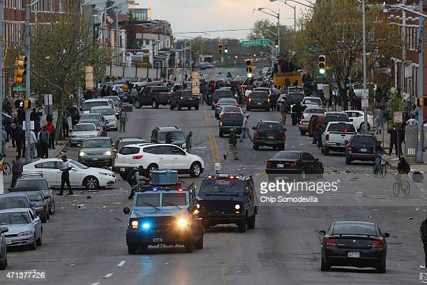 Armored cars drive down Pennsylvania Avenue as looters break into shops along the street following the funeral of Freddie Gray April 27 2015 in...