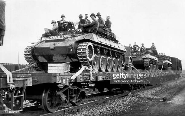Armored equipment is loaded on railroad cars for the blackout trip from the docks at Pusan to the war front Pusan South Korea July 27 1950 Troops...
