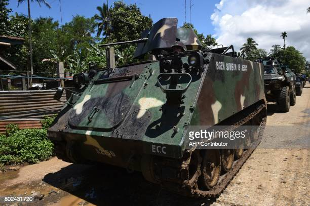 Armoured personnel carriers drive past a village on their way to the frontline in the outskirts of Marawi on the southern island of Mindanao on June...
