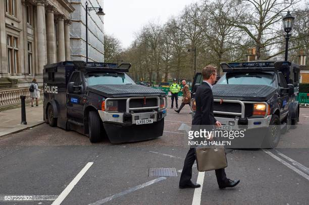 Armoured police personnel carriers are seen on a street leading to the Houses of Parliament in central London on March 24 2017 two days after the...
