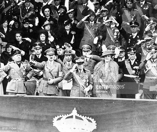 Arms akimbo premier Benito Mussolini views a parade of Italian might with his 'pal' Adolf Hitler King Victor Emmanuel and Queen Elena in Rome 1938...
