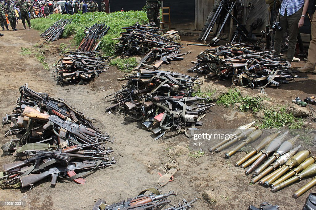 Arms and amunition of disarmed M23 rebels are displayed for the press on March 16, 2013 in Gasizi, 30km north of Gisenyi, at the border with Democratic Republic of Congo. Fighting between rival factions of Congolese rebel group M23 has sent hundreds of people, including many rebels, fleeing for neighbouring Rwanda, where the leader of one faction has been detained, Rwandan officials said on March 16.