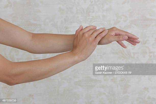 Arms of a woman in front of patterned wallpaper