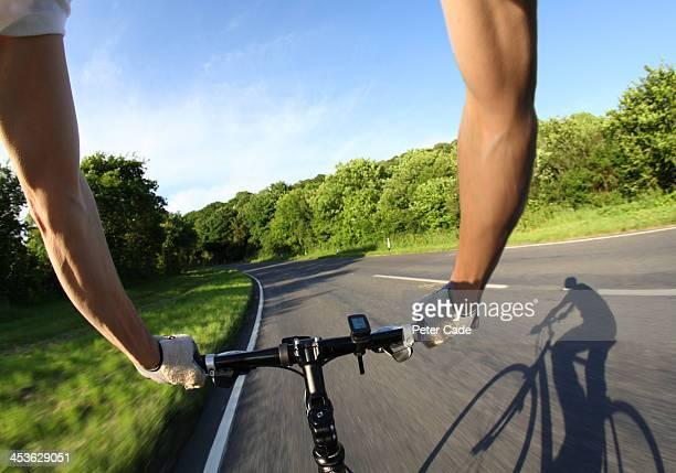 Arms of cyclist holding handlebars of bike