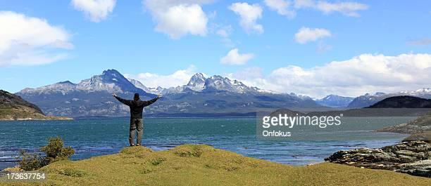 Bras en l'air homme de randonnée en bord de lac et les montagnes