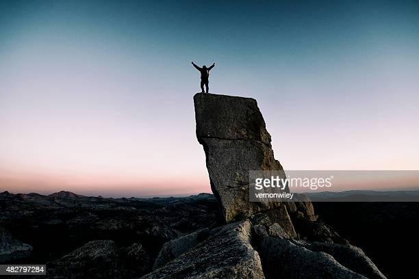 Arme hoch auf einer Felsspitze
