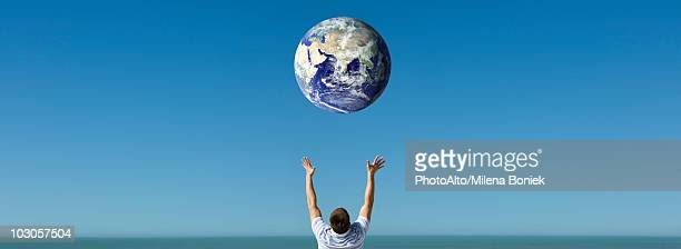 Arms raised reaching out to planet earth orbiting overhead