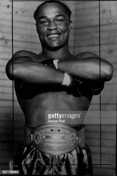 Armstrong Henry Wearing the belt which signifies that he is the only man ever to hold three world's boxing titles at one and the same time In mailing...