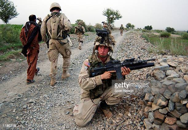 S Army 101st Airborne 3187 'Bravo' company soldiers escort an Afghan 'person under control' while conducting a sensitive site exploitation mission in...