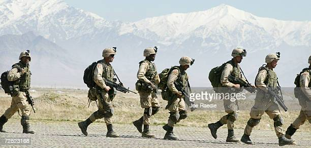 S Army 10th Mountain Division soldiers walk across the tarmac as they prepare to enter a Chinook helicopter March 13 2002 at the Bagram Air Base near...