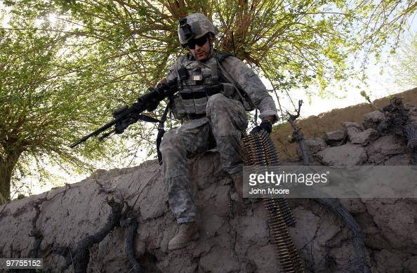 S Army 1LT Sgt Jonathan Hendricks carries machine gun ammunition while under fire on March 16 2010 at HowzeMadad in Kandahar province Afghanistan The...