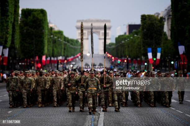 TOPSHOT US army 1st Division US air force US Navy and US Marines march down the Champs Elysees with the Arc de Triomphe in the background in Paris...